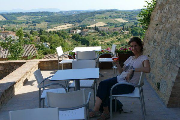 sitting at a table and chair, sipping red wine, overlooking the Tuscan hills