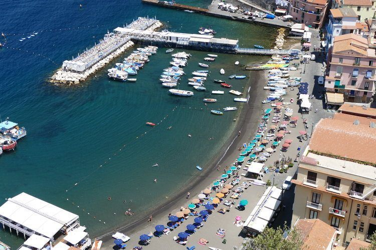 busy part of Amalfi coast, looking down onto a harbour and beach lined with umbrellas