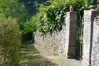 rocky garden path with a cobblestone wall on the right and tress on the left