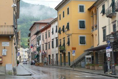 Main street of Bagni di Lucca with buildings in different earthy and pink shades