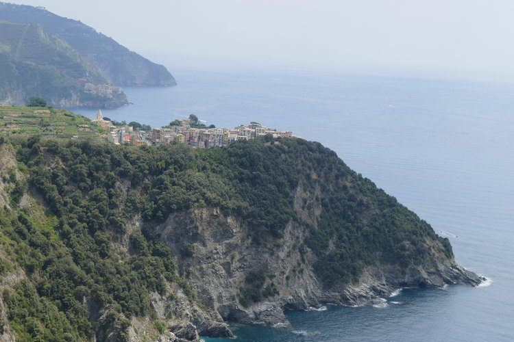 view of italian village perched on top of a rocky outcrop surrounded by deep blue sea