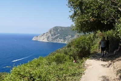walking along the cinque terre trail with views overlooking the deep blue sea