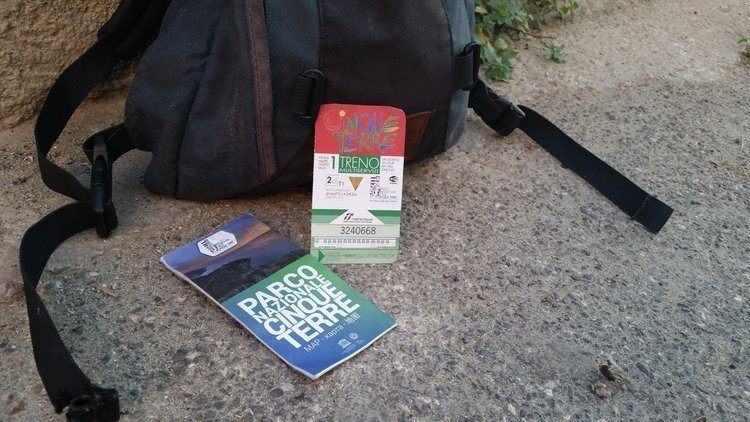 The Cinque Terre card and  map laying on the concrete path resting against a backpack