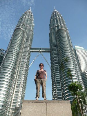 a female standing in between the Petronas towers from a below angle
