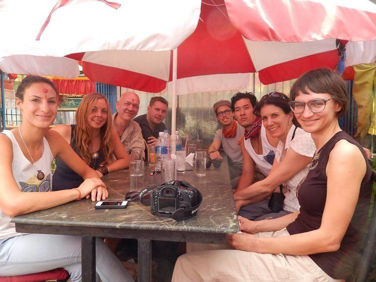 Group of male and female traveller sitting around a table under an umbrella sharing travel tips