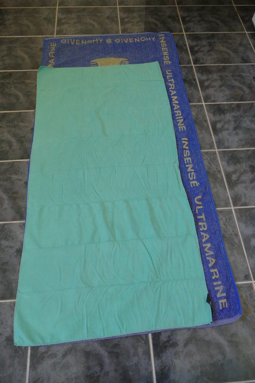 a chamios towel layed over the top of a medium sized towel.