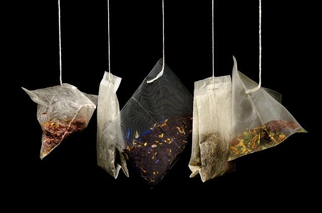 four herbal tea bags hanging from a wire