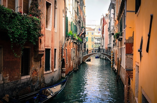 a canal in Venice city colour your travels by the rustic buildings