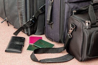 travel bags and suitcases with several passports and a travel wallet
