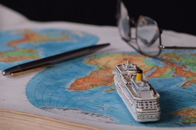 a toy ship sitting on a world map with pen and glasses
