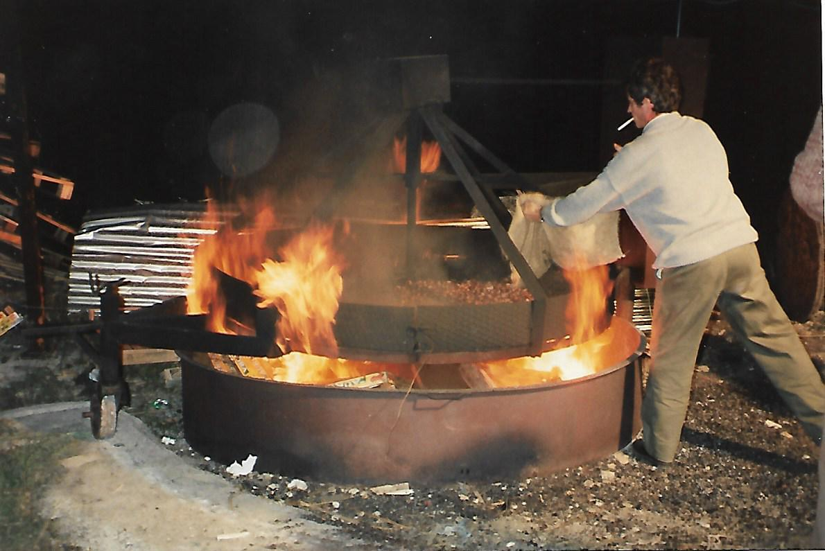 roasting chestnuts with a huge roaster over a fire part of the chestnut festivals in italy