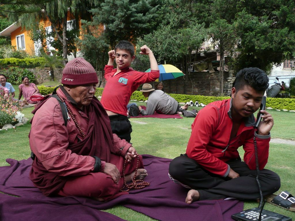A monk, a young boy flexing his arm muscles and a young guy trying to use a landline phone, all sitting in the middle of a garden