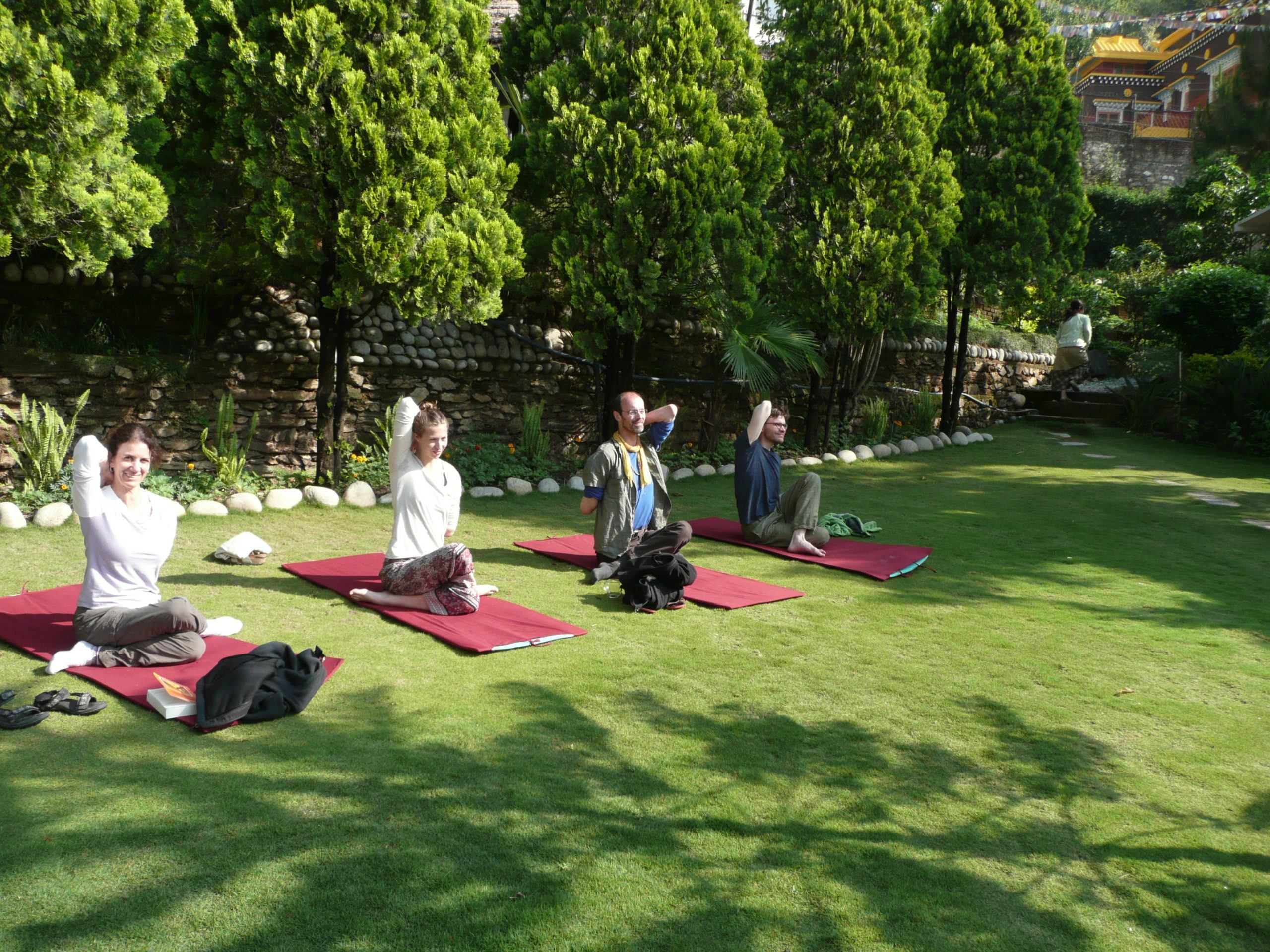 four people doing yoga on mats in a lush green garden, before the nepal earthquake