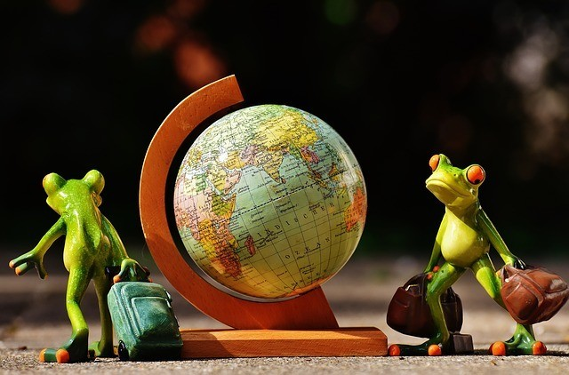 frogs carrying suitcases walking around a world globe