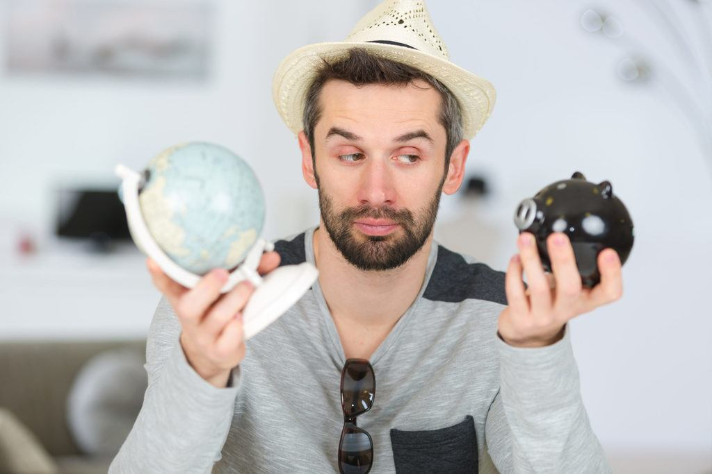 man holding world globe in one hand and a piggy bank in the other