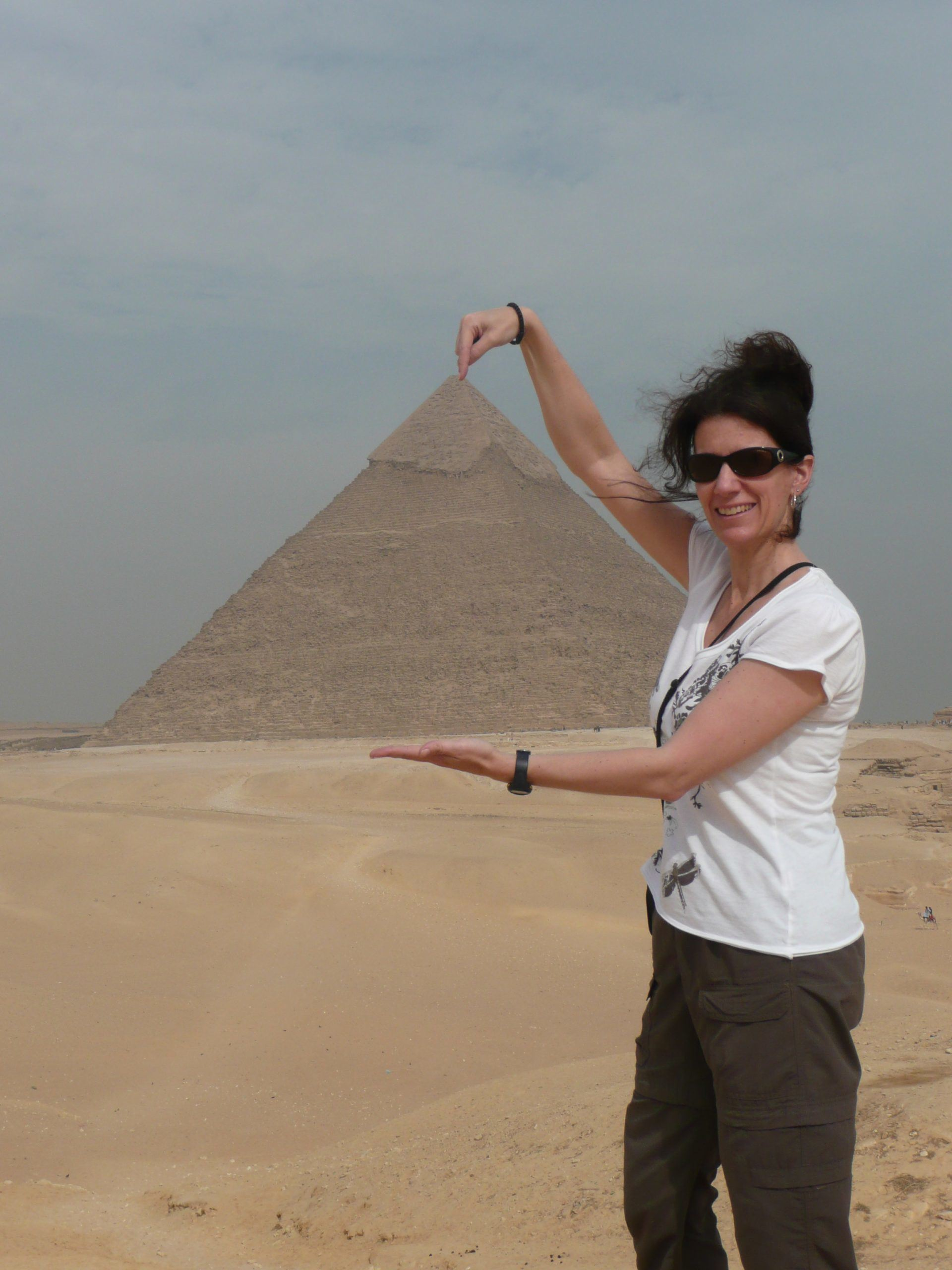 a female holding the giza pyramid between her hands while standing afar