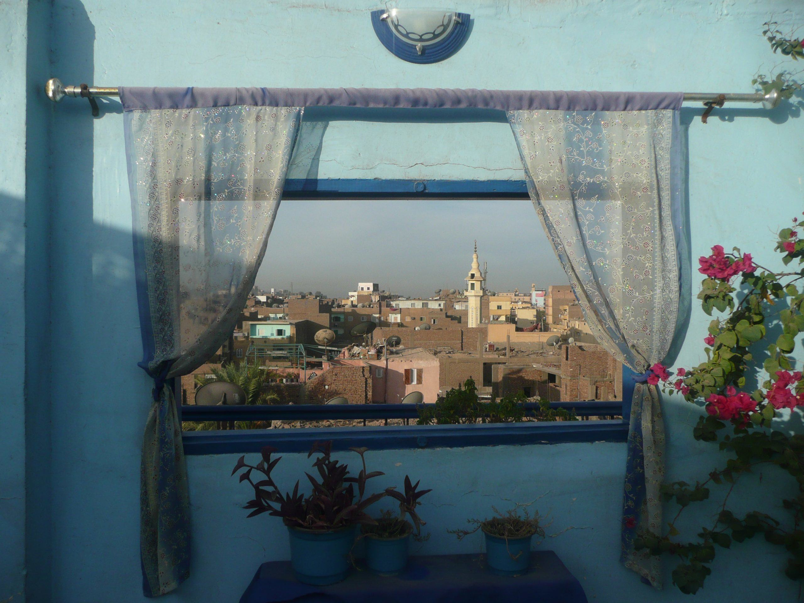 looking through a window into the old buildings of Luxor