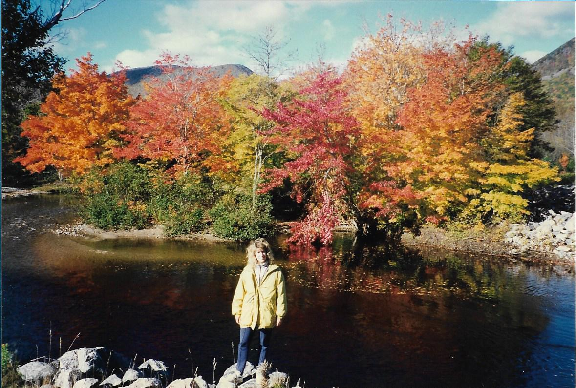 female standing in front of river with colourful trees in background - orange, yellow, red and green