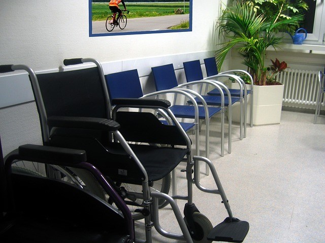 doctors waiting room with empty blue chairs lined up against the wall and one wheelchair