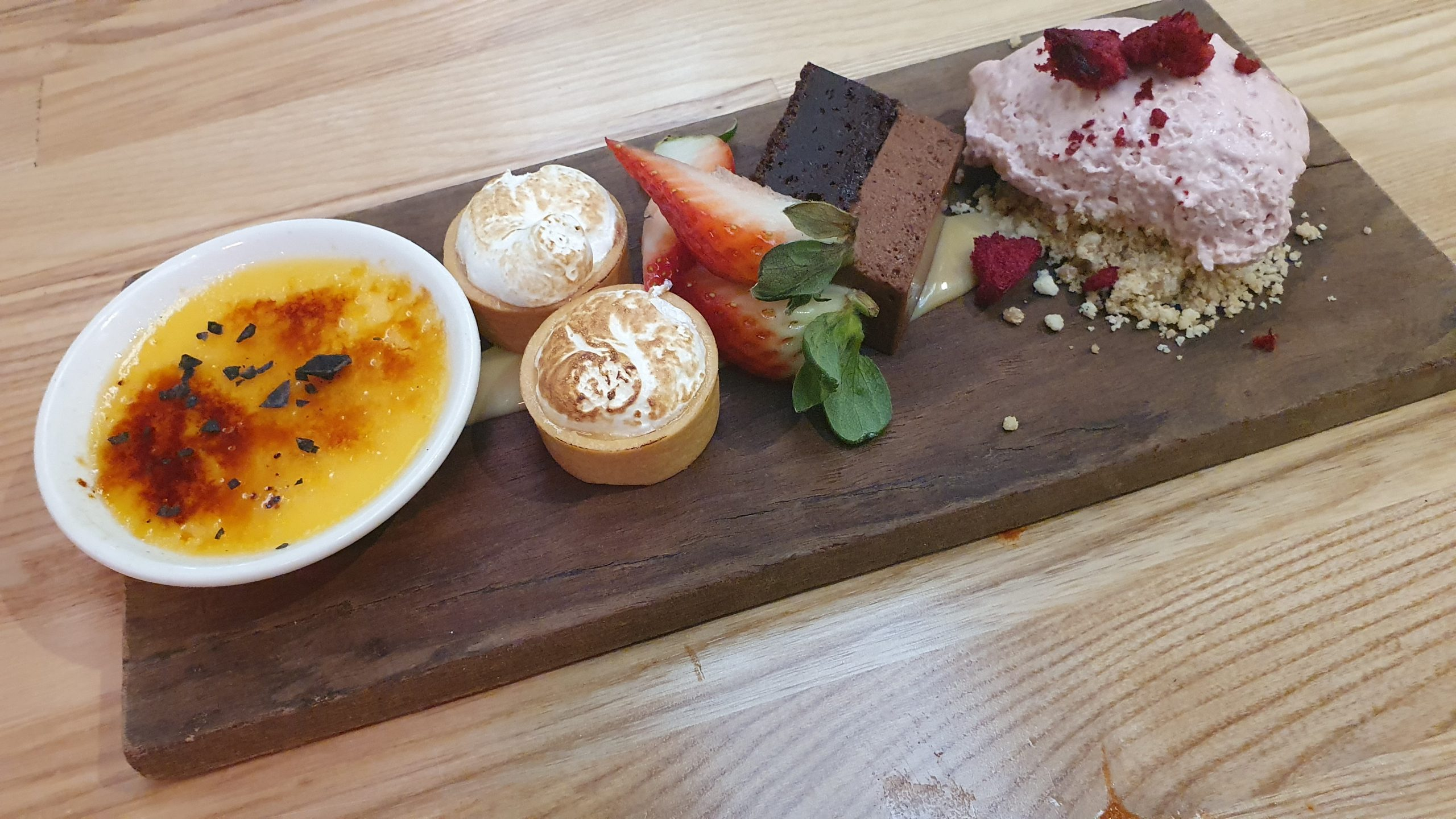 5 different desserts of different colours displayed in a row on a wooden board