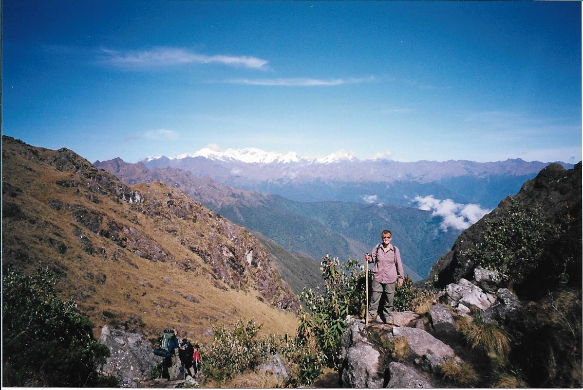 a female hiker standing at the top of a mountain pass following hiking trails