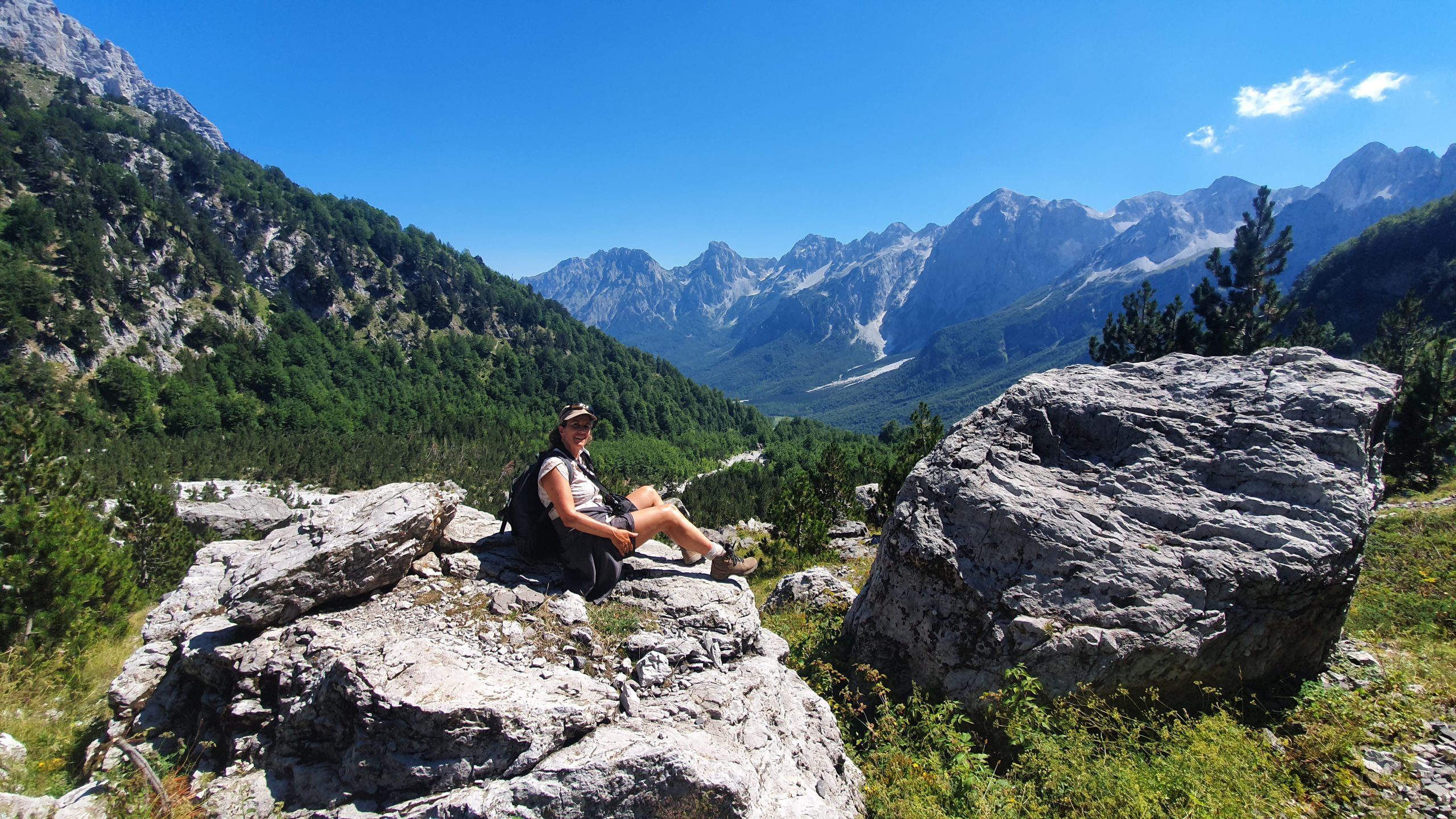 female hiker sitting on rock over lookin moutaineous valley on the valbona to theth hiking trails