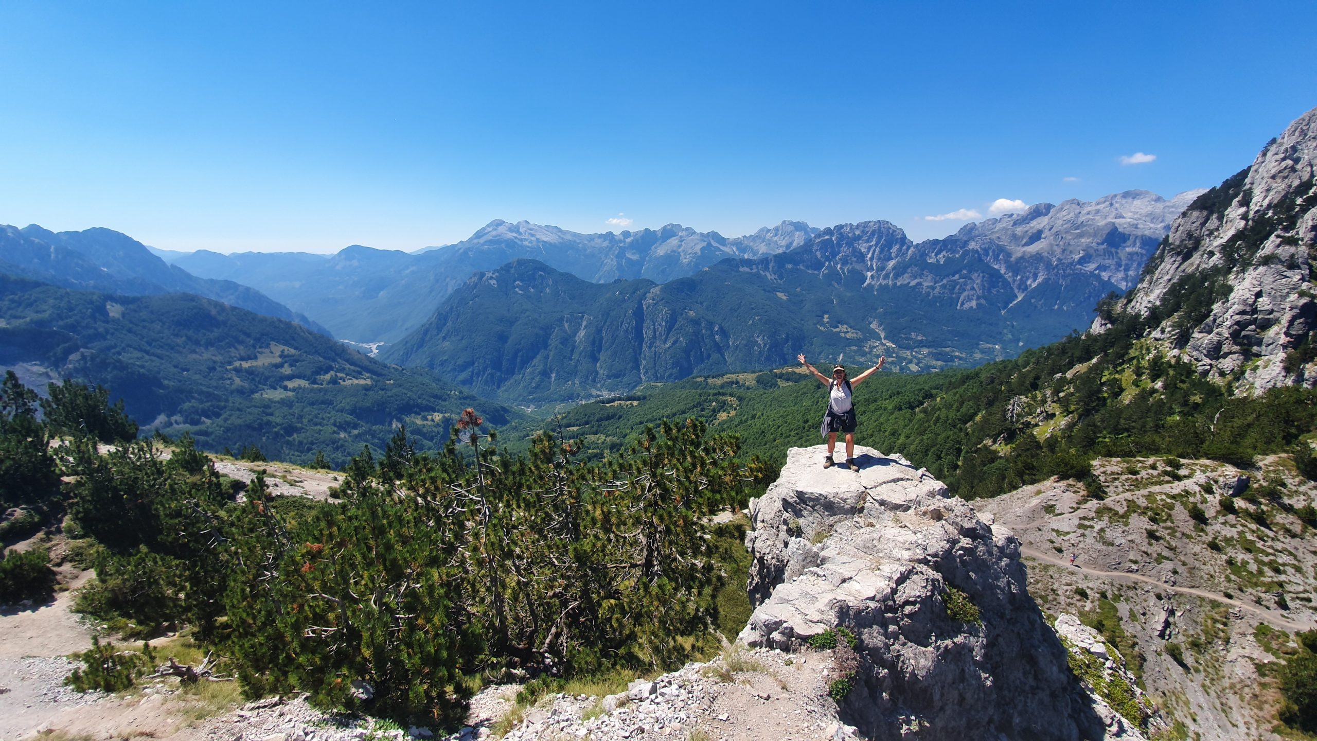 female hiker standing on a rocky outcrop overlooking the entire mountain range and valley, on the Valbona-Theth hiking trails