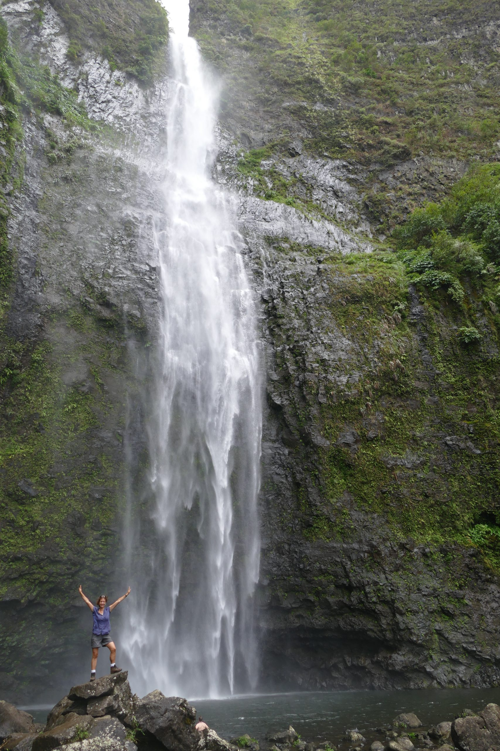 female hiker standing on rocks looking very small against the backdrop of a very high waterfall